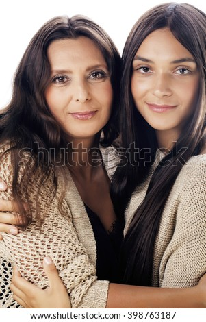 cute pretty teen daughter with mature mother hugging, fashion style brunette makeup close up tann mulattos, warm colors - stock photo