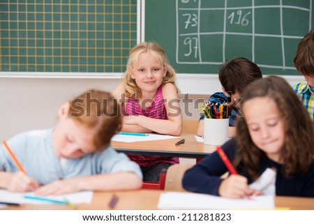 Cute pretty young blond girl in class st the back of the classroom grinning happily at the camera with selective focus past other students in the foreground - stock photo