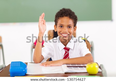 cute primary schoolboy hand up in classroom - stock photo
