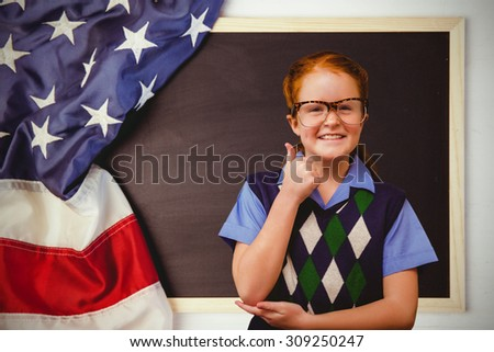 Cute pupil dressed up as teacher against american flag on chalkboard - stock photo