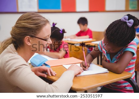 Cute pupil getting help from teacher in classroom at the elementary school - stock photo