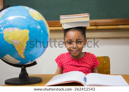 Cute pupil holding books on her head at elementary school - stock photo