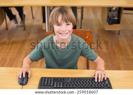 Cute pupil in computer class at the elementary school - stock photo