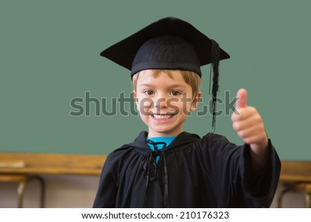Cute pupil in graduation robe smiling at camera in classroom at the elementary school - stock photo