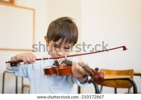 Cute pupil playing violin in classroom at the elementary school - stock photo