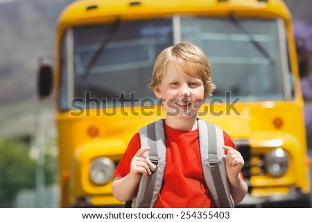 Cute pupil smiling at camera by the school bus outside the elementary school - stock photo