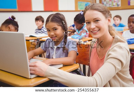 Cute pupil using computer with teacher at the elementary school - stock photo