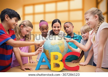 Cute pupils and teacher looking at globe in library against room with large windows showing city - stock photo