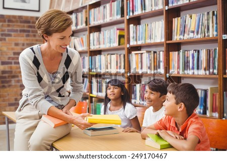 Cute pupils and teacher looking for books in library at the elementary school - stock photo