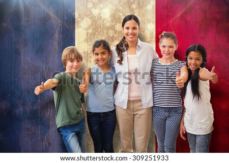 Cute pupils and teacher smiling at camera in computer class against france flag in grunge effect - stock photo