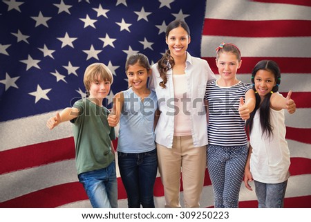 Cute pupils and teacher smiling at camera in computer class against united states of america flag - stock photo