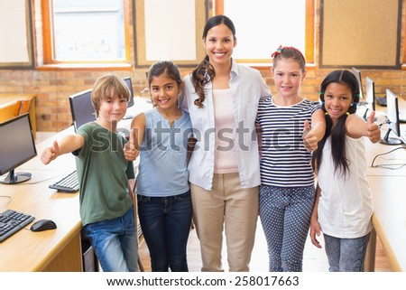Cute pupils and teacher smiling at camera in computer class at the elementary school - stock photo