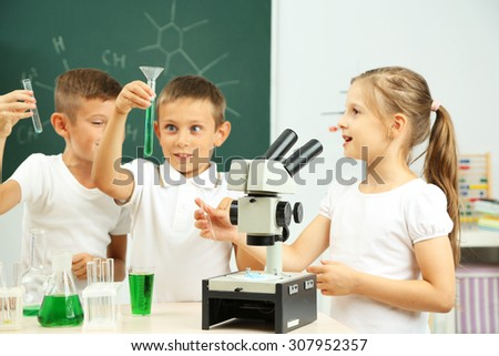 Cute pupils doing biochemistry research in chemistry class - stock photo