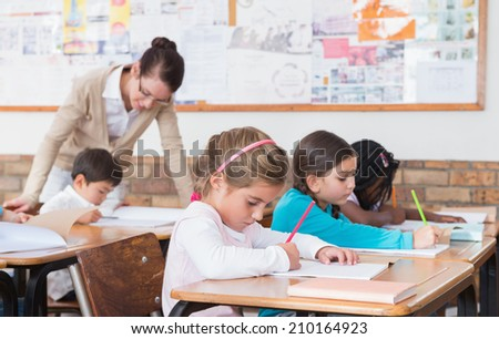 Cute pupils drawing at their desks at the elementary school - stock photo