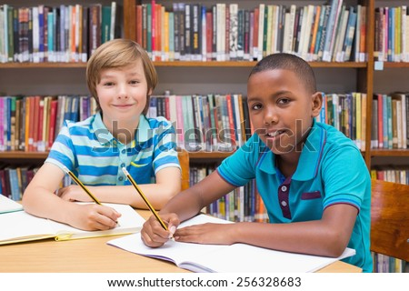 Cute pupils drawing in library at the elementary school - stock photo