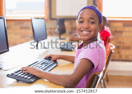 Cute pupils in computer class at the elementary school - stock photo