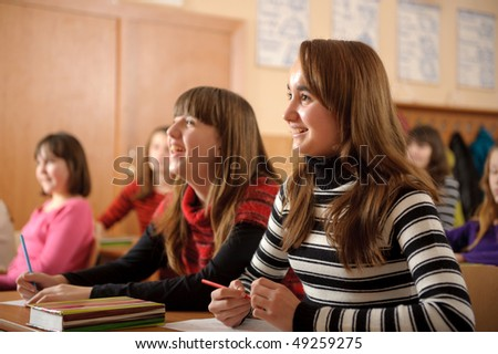 Cute pupils is smiling and laughing during lesson - stock photo