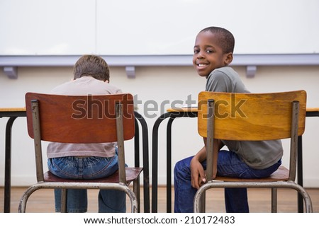 Cute pupils listening attentively in classroom at the elementary school - stock photo
