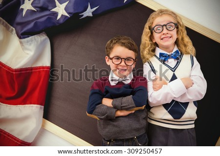 Cute pupils looking at camera against american flag on chalkboard - stock photo