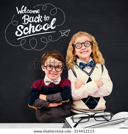 Cute pupils looking at camera against blackboard - stock photo