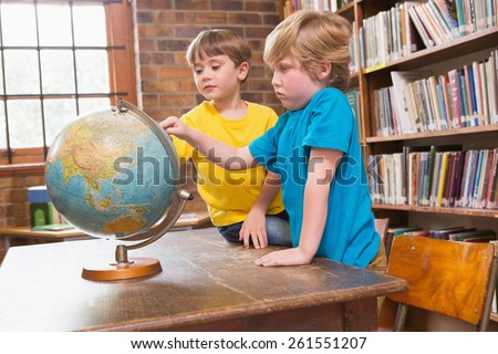 Cute pupils looking at globe at elementary school - stock photo