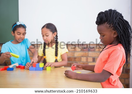Cute pupils playing with building blocks at the elementary school - stock photo