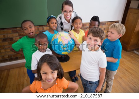 Cute pupils pointing to globe in classroom at the elementary school - stock photo