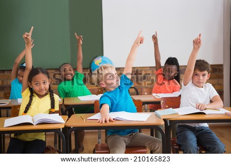 Cute pupils raising their hands at the elementary school - stock photo
