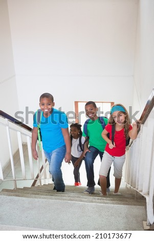 Cute pupils smiling and walking up stairs at the elementary school - stock photo