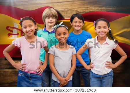 Cute pupils smiling at camera in classroom against digitally generated spain flag rippling - stock photo