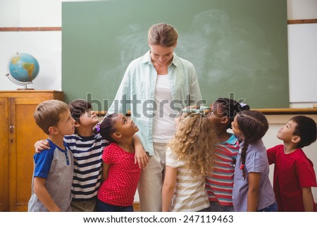 Cute pupils smiling at camera in classroom at the elementary school - stock photo