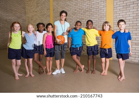 Cute pupils smiling at camera with PE teacher at the elementary school - stock photo