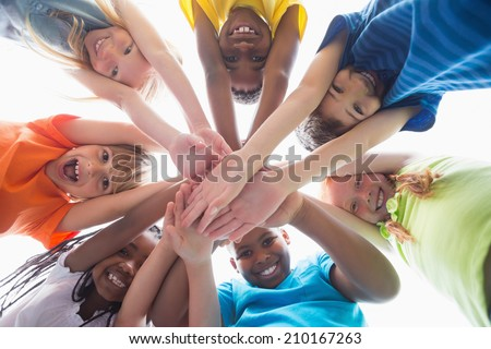 Cute pupils smiling down at camera outside at the elementary school - stock photo