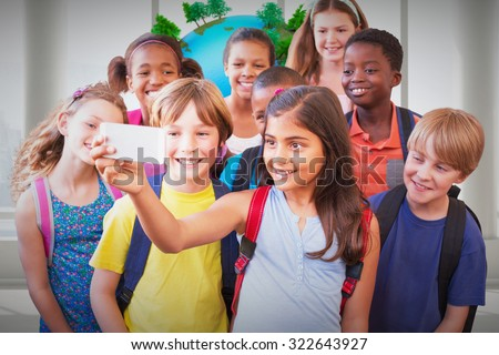 Cute pupils using mobile phone against earth floating in room - stock photo