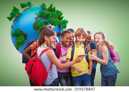 Cute pupils using mobile phone against green vignette - stock photo