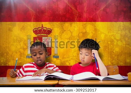 Cute pupils writing at desk in classroom against spain flag in grunge effect - stock photo