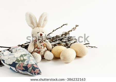 cute rabbit and willow branches with buds and wooden eggs on white background, holiday card concept, easter theme minimalistic - stock photo