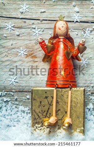 Cute retro style wooden Christmas angel in a colorful red dress sitting on a decorated gold block nestling in snow with falling snowflake decorations on a rustic wooden wall with copyspace - stock photo