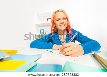 Cute school age girl doing homework writing in textbook  - stock photo
