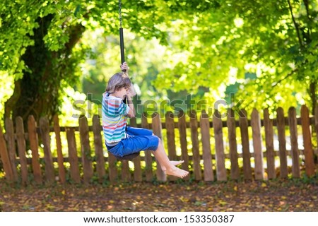 Cute school boy enjoying a swing ride on a playground on a warm sunny summer day - stock photo