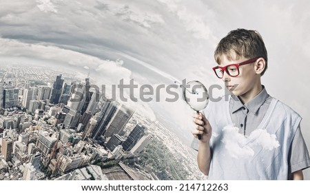 Cute school boy examining objects with magnifying glass - stock photo