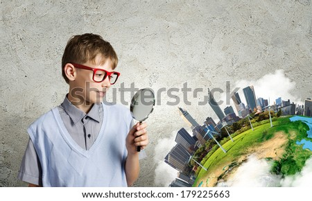 Cute school boy examining objects with magnifying glass. Elements of this image are furnished by NASA - stock photo