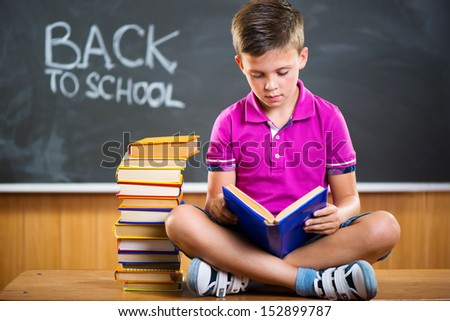 Cute school boy reading book in classroom against blackboard - stock photo