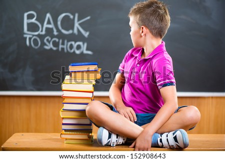 Cute school boy sitting with books against blackboard in classroom - stock photo