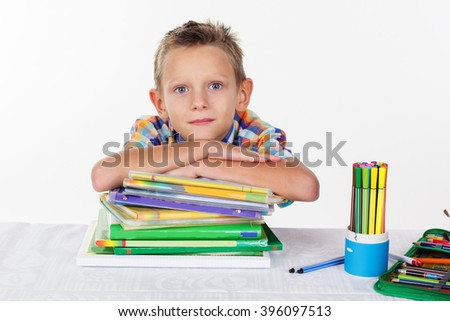 Cute school boy with pile of books - stock photo
