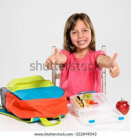 Cute school girl gives the thumbs up for school and a healthy lunch box - stock photo