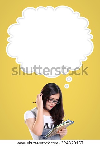 Cute school girl scratching her head in confusion, with empty thought cloud for copy space above her, over yellow background. Education concept in comic style design ready to use - stock photo