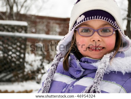 cute school girl with glasses bundled up in winter, smiling at camera with school in the background - stock photo