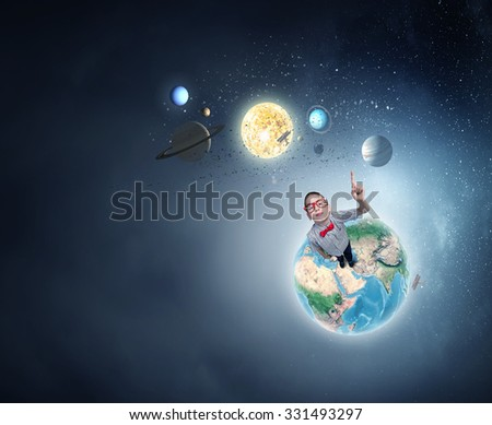 Cute schoolboy in red glasses with finger pointing up. Elements of this image are furnished by NASA - stock photo