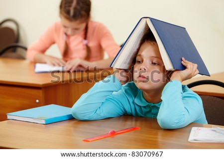 Cute schoolboy keeping open book on head in classroom - stock photo